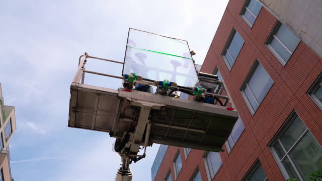 team of blue-collar workers delivering the double-glass to the installation place on the lifting platform. - replacement stock videos & royalty-free footage
