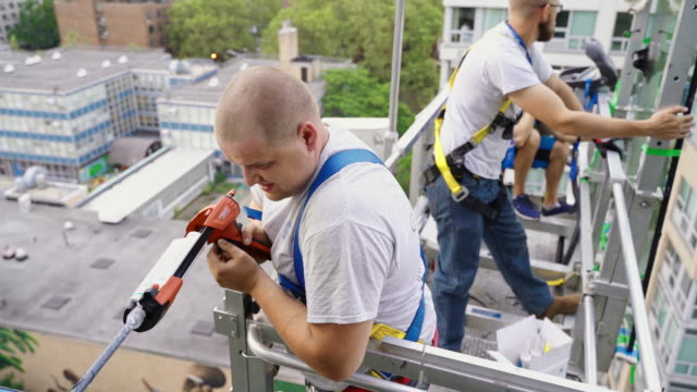 team of blue-collar workers replacing a broken window in the office building - applying a fresh sealant for a new glass installation. high-altitude work on the lifting platform which is placed outside. - hoisting stock videos & royalty-free footage