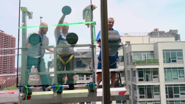 オフィスビルの壊れた窓を置き換えるブルーカラーの労働者のチーム - 古い壊れたガラスを取り除きます。外に置かれる持ち上がるプラットホームの高高度の仕事。 - 交代点の映像素材/bロール