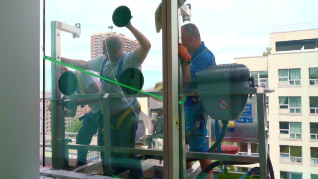 team of blue-collar workers replacing a broken window in the office building - removing the old broken glass. high-altitude work on the lifting platform which is placed outside. - hoisting stock videos & royalty-free footage