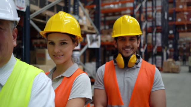 team of business people and warehouse supervisors standing behind their confident female leader at a warehouse all smiling at camera - world trade organisation stock videos & royalty-free footage