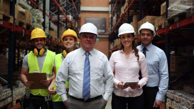 Team of business people and warehouse workers at a warehouse all standing while facing camera very cheerfully
