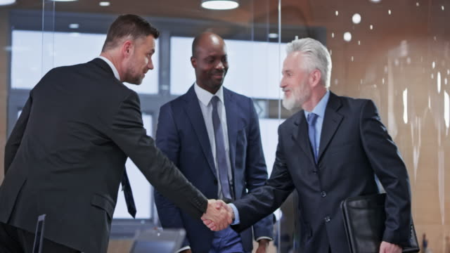team of business people entering the meeting room and shaking hands - business meeting stock videos & royalty-free footage