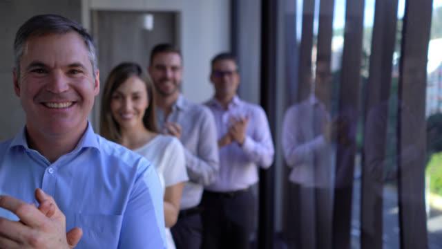 vidéos et rushes de équipe de gens d'affaires restant dans une ligne applaudissant tout en faisant face au sourire d'appareil-photo - salle de réunion