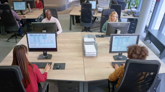 cs ld team of call centre agents taking incoming calls at their workstations - form of communication stock videos & royalty-free footage