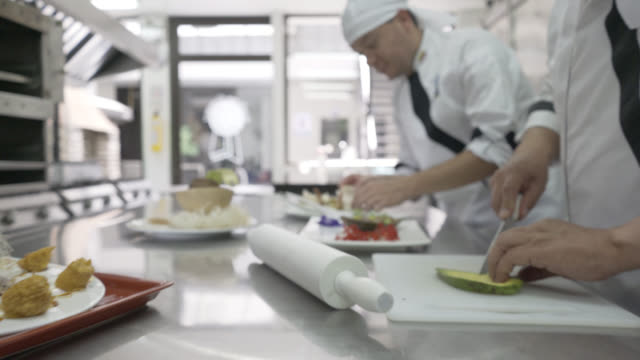 team of cooking staff preparing a meal working in line - kitchen stock videos & royalty-free footage