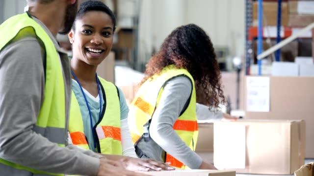 team vertrieb lagerarbeiter qualitätskontrolle vor dem versenden von paketen durchführen - distribution warehouse stock-videos und b-roll-filmmaterial