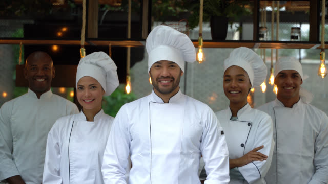 team of diverse kitchen staff facing camera smiling - chef stock videos & royalty-free footage