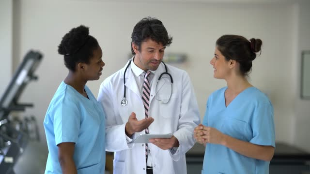 Team of doctor and nurses at the clinic discussing the medical chart of a patient displayed on the computer tablet