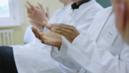 Team of doctors applauding after presentation at hospital
