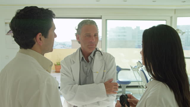 vídeos de stock, filmes e b-roll de ds team of doctors in conversation in doctor's practice, camera moves 360 degrees around them - câmera em movimento