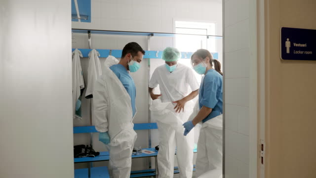 team of doctors or nurses taking off the protective equipment in hospital changing room after a long day of work - removing stock videos & royalty-free footage
