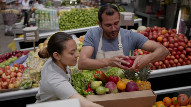 team of employees at a fresh produce stall organizing a delivery for customer in a reusable cardboard box - market trader stock videos & royalty-free footage