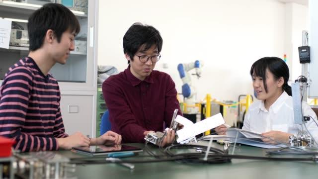 team av teknologer - robotarm tillverkningsutrustning bildbanksvideor och videomaterial från bakom kulisserna
