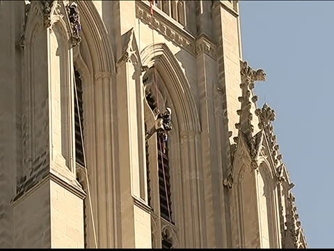 vídeos de stock e filmes b-roll de team of engineers and architects rappel downwards from the top of the national cathedral to inspect for any possible damage from the august 2011... - 12 15 meses