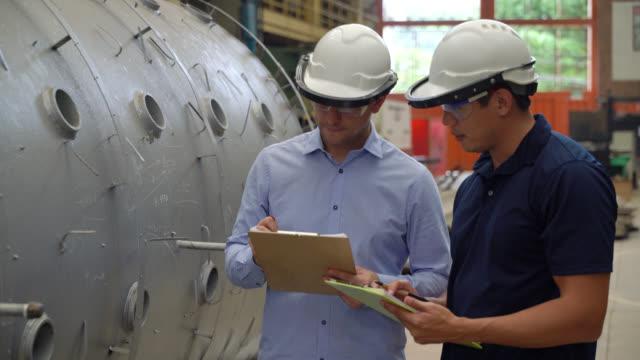team von ingenieuren, die eine metallgebaute struktur überprüfen, während sie in einer metallurgischen fabrik zwischenden schneidig sprechen und halten - visit stock-videos und b-roll-filmmaterial
