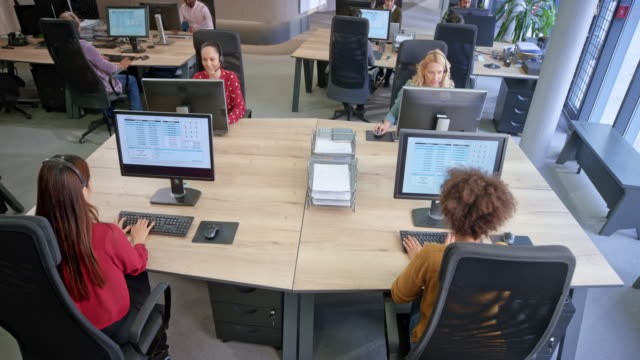 cs a team of female agents in the call centre working at their stations - telecommunications worker stock videos & royalty-free footage