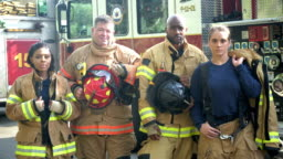 Team of firefighters standing in front of fire truck
