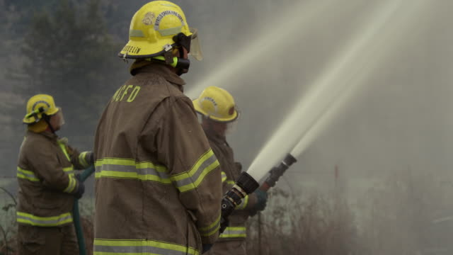 a team of firefighters using high pressure hoses - firefighter stock videos & royalty-free footage