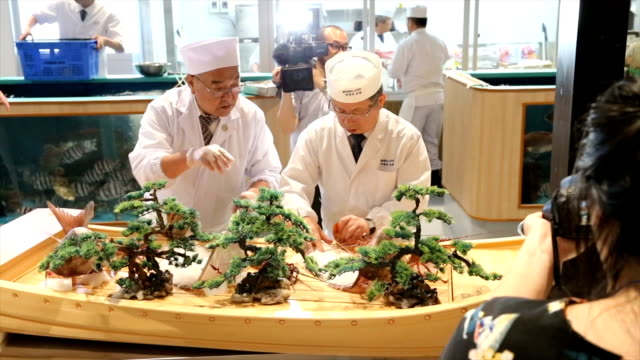 a team of fishmongers demonstrated their manual dexterity by slicing up a large tuna for members of the international media who arrived here ahead of... - g7サミット点の映像素材/bロール