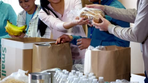team of food bank volunteers pack donated food item during food drive - paper bag stock videos & royalty-free footage