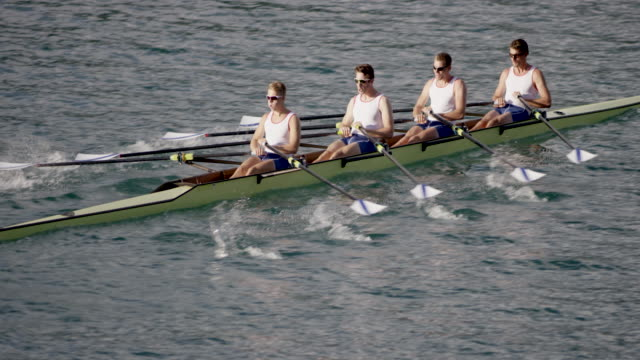 SLO MO Team of four male athletes gliding across a lake in a quad scull