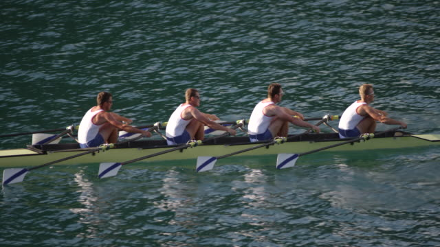 SLO MO Team of four male athletes sculling across a lake