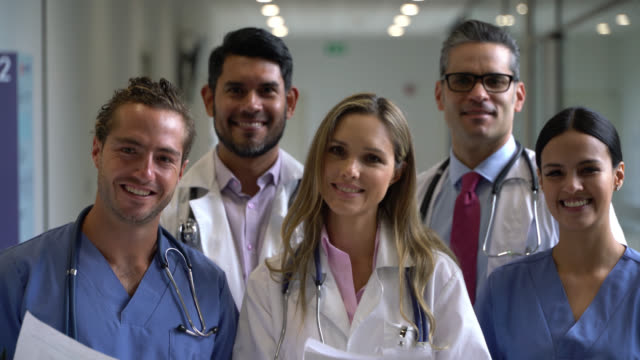 team of healthcare professionals at the hospital holding paperwork and smiling at camera - medical occupation stock videos & royalty-free footage