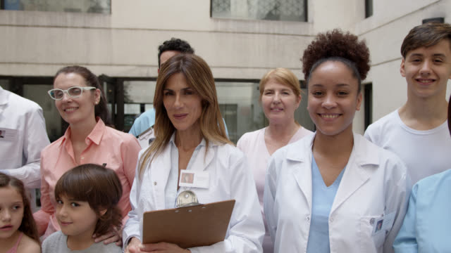 team of healthcare workers and patients standing at the patio of a clinic all smiling at camera - laboratory coat stock videos & royalty-free footage