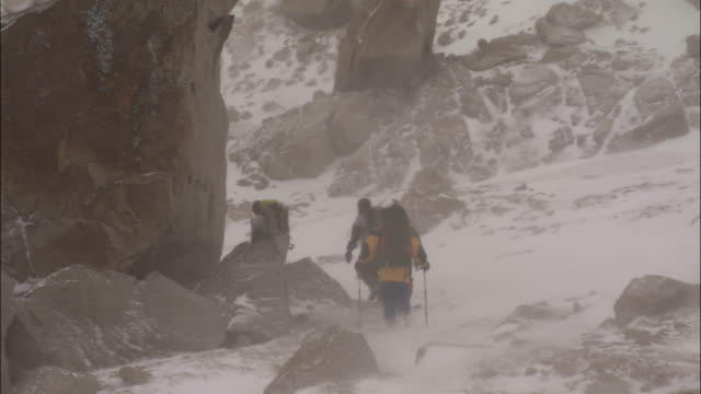 a team of hikers walk through snow in the mountains. - provincial reconstruction team stock videos & royalty-free footage