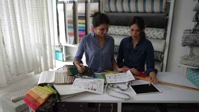 Team of interior designers working on a decor of a room while looking at a plan and a fabric swatch