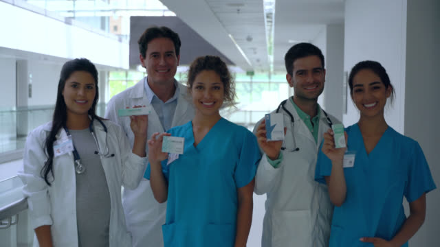 team of latin american professional healthcare workers at the hospital facing camera smiling holding prescription medicine - males stock videos & royalty-free footage