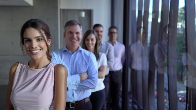 vidéos et rushes de équipe d'avocats restant dans une ligne tout en faisant face à la caméra souriant avec confiance - avocat juriste