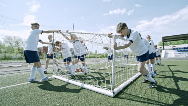 Team of little athletes pulling soccer goals