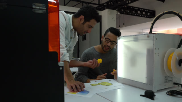 team of male designers working on a plastic container design with the 3d printer - tecnico video stock e b–roll