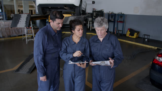 team of mechanics discussing the job done on cars while looking at lists on clipboards at an auto repair shop - overalls stock videos & royalty-free footage