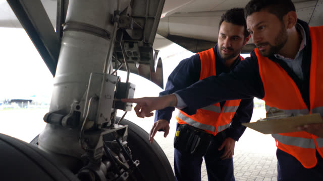 team of mechanics doing inspection of an airplane looking at a checklist while pointing at different parts - aggiustare video stock e b–roll