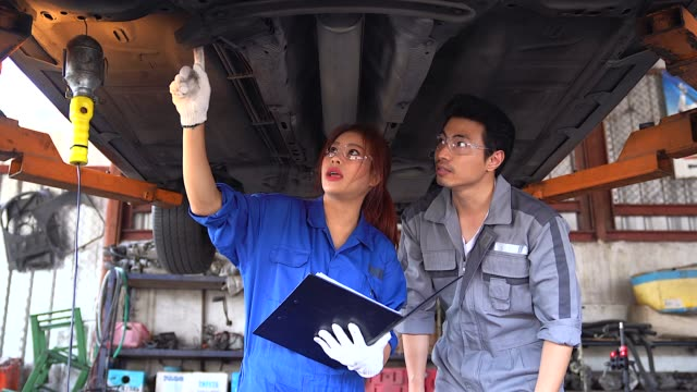 a team of mechanics men and women working together at the repair garage. - mechanic stock videos & royalty-free footage
