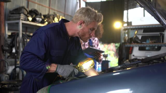 stockvideo's en b-roll-footage met a team of mechanics men and women working together at the repair garage. - men