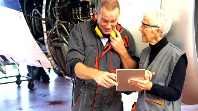 mechaniker mit digital-tablette am flugzeughangar-team - air vehicle stock-videos und b-roll-filmmaterial