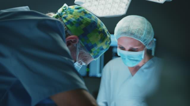 vidéos et rushes de équipe de collègues médicaux opérant patient dans l'usi - operating