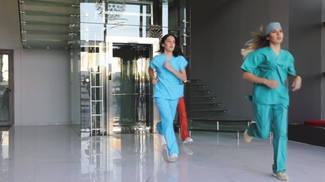 team of medical professionals rush about for emergency in hospital corridor - urgency stock videos & royalty-free footage