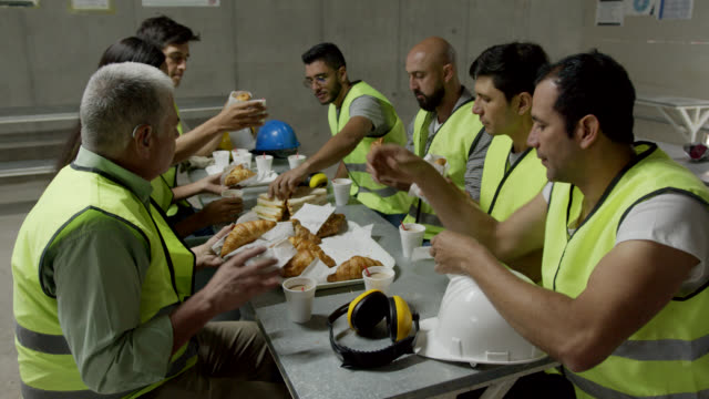 team of people at a construction site enjoying a snack while smiling and talking - french food stock videos & royalty-free footage