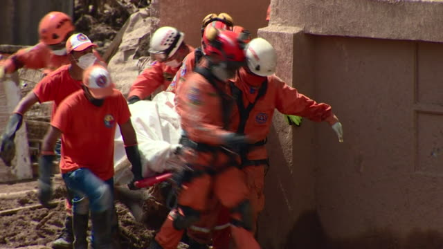 A team of people removing a dead body from rubble after a devastating landslide in Mocoa Colombia