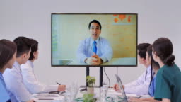 Team of physicians on a video conference call with a male colleague.Group young interns listening to doctor's lecture during medical conference.High-Tech Meetings, health care, medical education, people and medicine concept.Education Topics