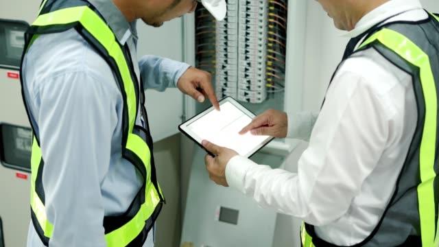 team professioneller ingenieure, die maschine am werksarbeitsplatz überprüfen - ingenieurwesen stock-videos und b-roll-filmmaterial