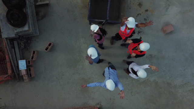 team of professionals at a construction site in a huddle celebrating - aerial view - stereotypically working class stock videos & royalty-free footage