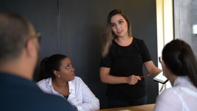 vídeos de stock e filmes b-roll de team of professionals discussing over new business project - workshop