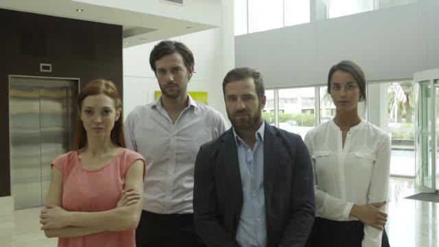 vídeos y material grabado en eventos de stock de team of professionals in lobby portrait - cuatro personas