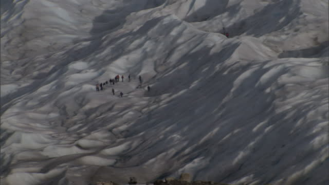 a team of rescuers stand in a circle on a glacier. - survival stock videos & royalty-free footage